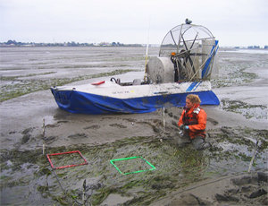 Woman standing in mud near boat